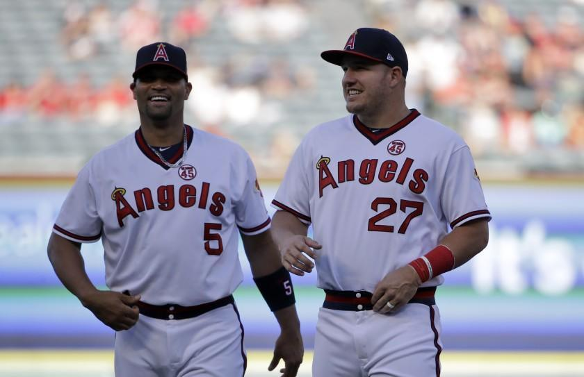 The Angels' Mike Trout, right, and Albert Pujols smile before a game against the Chicago White Sox on Aug. 17, 2019.