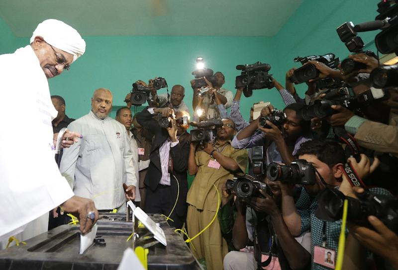 Journalists take images as Sudanese President and candidate in the presidential elections Omar al-Bashir (L) casts his vote at a polling station in the Saint Francis school in Khartoum on April 13, 2015 (AFP Photo/Patrick Baz)