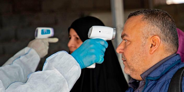A medic takes a the temperature of Iraqi at the Shalamjah border crossing between Iran and Iraq on February 21, 2020.