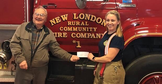 Angie Arsenault delivers a 50-50 cheque at New London fire station. That's her dad, Jim Arsenault. (Submitted by Angie Arsenault - image credit)