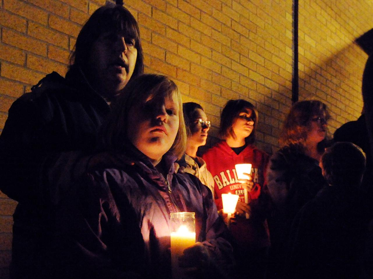 Ahna McCue and her daughter Emily attend a candlelight vigil, Sunday, Nov. 11, 2012, at Southwest Elementary School in Greenwood, Ind., for teacher Jennifer Longworth. Officials did not identify the two people who were killed in a blast on Saturday. However, a candlelight vigil was held for second-grade teacher Jennifer Longworth. She and her husband, John Dion Longworth, lived at a home destroyed in the blast. (AP Photo/The Indianapolis Star, Rob Goebel)