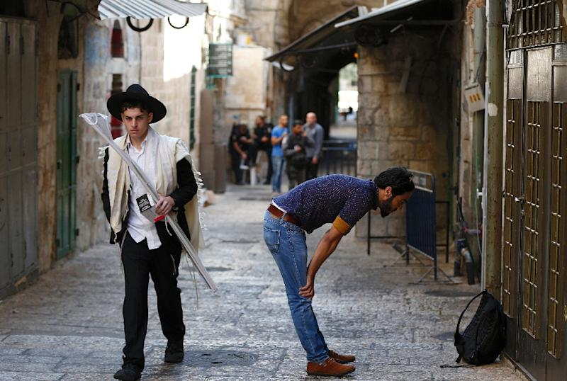 An ultra-Orthodox Jew (L) walks past a Palestinian Muslim, praying in Jerusalem's Old City on September 29, 2015