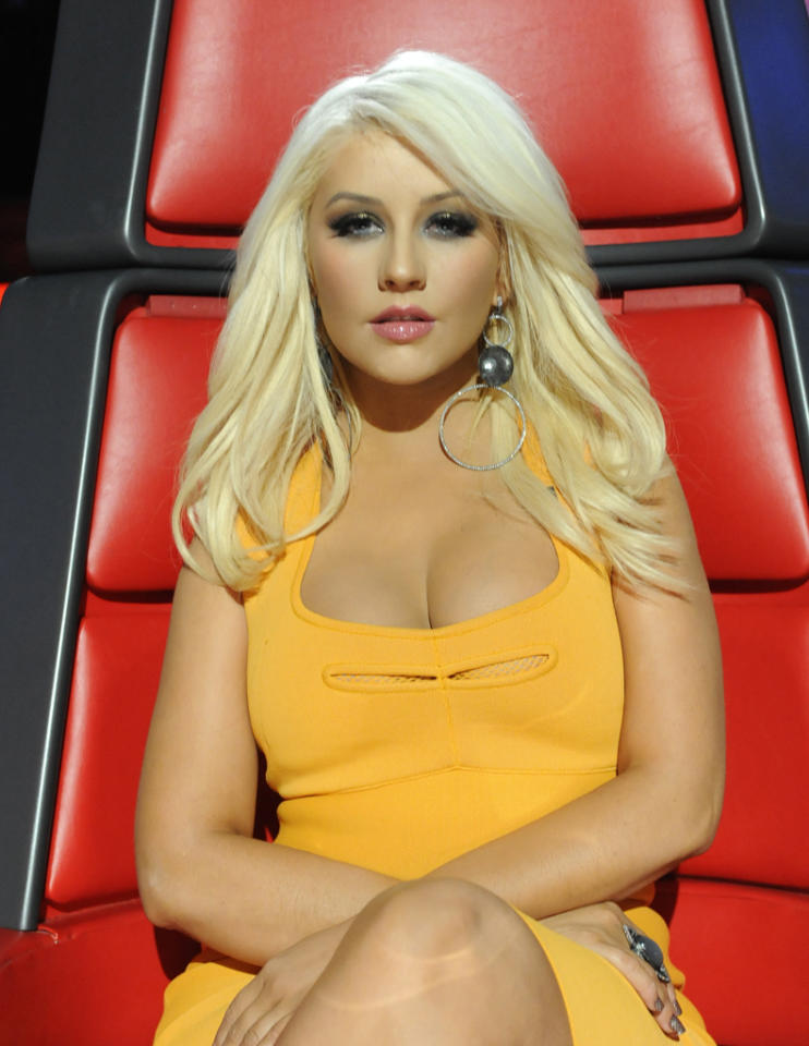 "<p class=""MsoNormal"">One of her standout looks was this marigold, form-fitting, cleavage-teasing dress, which she accessorized with studded Louboutin stilettos. ""Our glam revolved around the color of my dress,"" Aguilera later wrote on her website. ""I thought it was fresh and bright and I wanted to be sure my hair and makeup complemented the color rather than clashed with it.""</p>"
