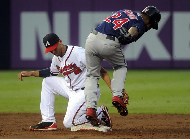 Atlanta Braves shortstop Andrelton Simmons, left, is late on the tag on Cleveland Indians' Michael Bourn who steals second base during the third inning of a baseball game on Thursday, Aug. 29, 2013, in Atlanta. (AP Photo/John Amis)