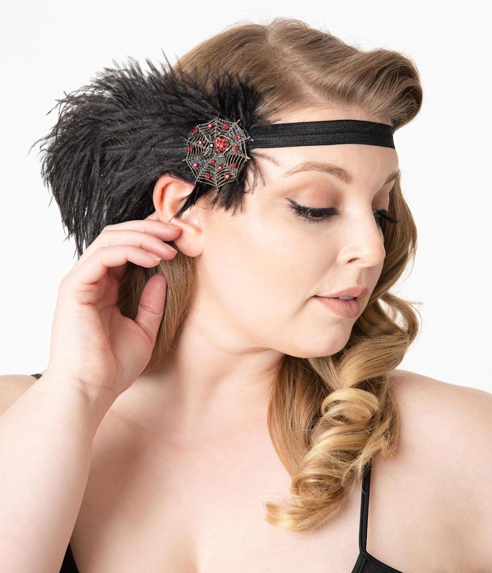 <p>Party like Gatsby in this <span>1920s Style Black Feather Spider Web Headband</span> ($42).</p>