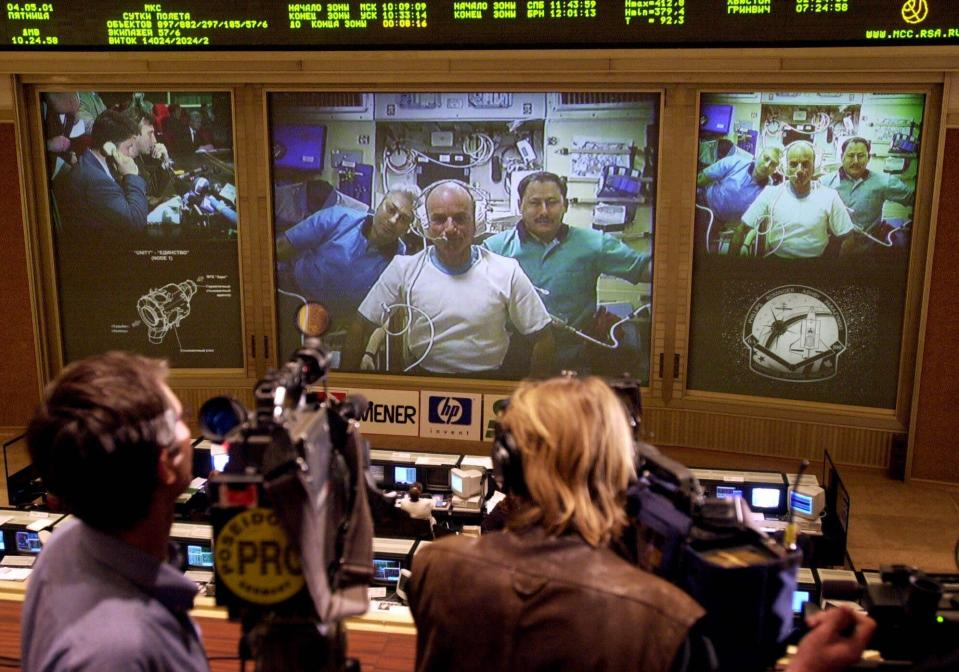 FILE - In this Friday, May 4, 2001 file photo, reporters and officials at the Mission Control Center in Korolev, Russia, outside Moscow, watch U.S. space tourist, Californian businessman Dennis Tito speaking from inside the International Space Station. Russian cosmonauts Yuri Baturin, left on the screen, and Talgat Musabayev, right, listen. Tito paid $20 million to visit the space station, launching atop a Russian rocket. Virginia-based Space Adventures arranged his weeklong trip, as well as seven more tourist flights that followed. (AP Photo/Maxim Marmur)