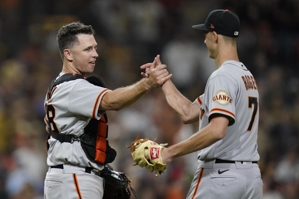 San Francisco Giants catcher Buster Posey, left, celebrates with relief pitcher Tyler Rogers after the Giants defeated the San Diego Padres 6-5 in a baseball game Tuesday, Sept. 21, 2021, in San Diego. (AP Photo/Gregory Bull)