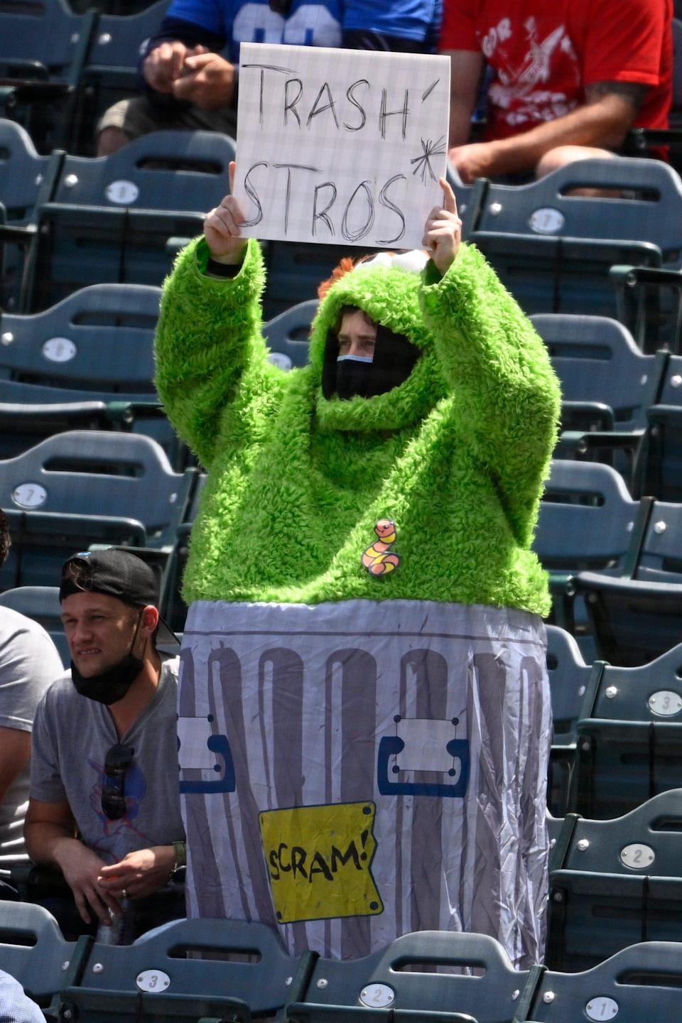 An Angels fan holds up a sign wearing an Oscar the Grouch costume during a game against the Astros at Angel Stadium.