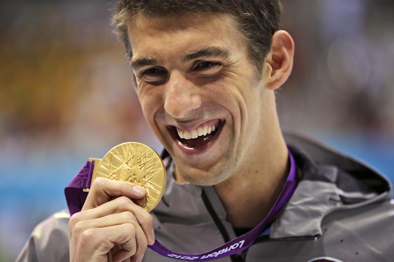 FILE - In this Aug. 3, 2012, file photo, United States' Michael Phelps displays his gold medal for the men's 100-meter butterfly swimming final at the Aquatics Centre in the Olympic Park during the 2012 Summer Olympics in London. Phelps is coming out of retirement, the first step toward possibly swimming at the 2016 Rio Olympics. Bob Bowman, the swimmer's longtime coach, told The Associated Press on Monday, April 14, 2014, that Phelps is entered in three events — the 50- and 100-meter freestyles and the 100 butterfly at his first meet since the 2012 London Games at a meet in Mesa, Ariz., on April 24-26. (AP Photo/Matt Slocum, File)