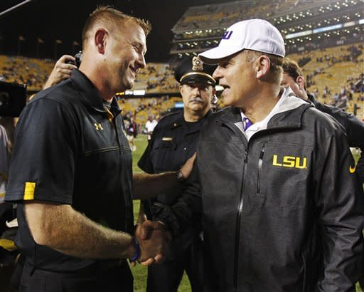Towson coach Rob Ambrose, left, shakes hands with LSU coach Les Miles after an NCAA college football game in Baton Rouge, La., Saturday, Sept. 29, 2012. LSU defeated Towson 38-22. (AP Photo/Bill Haber)