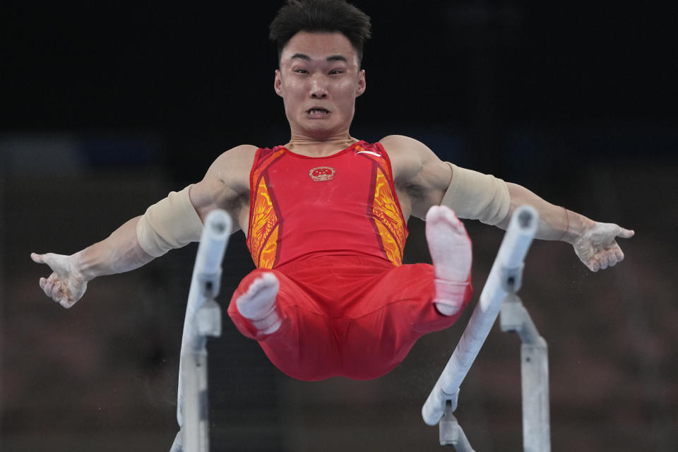 Sun Wei, of China, performs on the parallel barsduring the artistic men's team final at the 2020 Summer Olympics, Monday, July 26, 2021, in Tokyo. (AP Photo/Natacha Pisarenko)