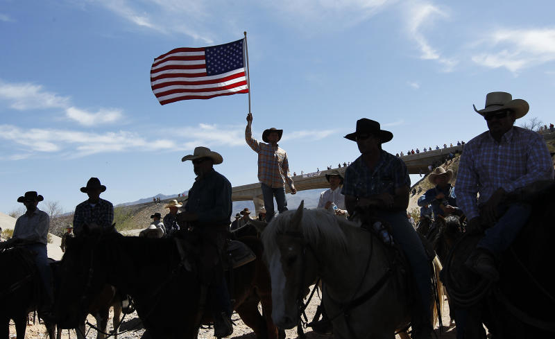 A supporter of the Bundy family flies the American flag after the Bureau of Land Management agreed to release the Bundy's cattle near Bunkerville, Nev. April 12, 2014. (AP Photo/Las Vegas Review-Journal, Jason Bean)