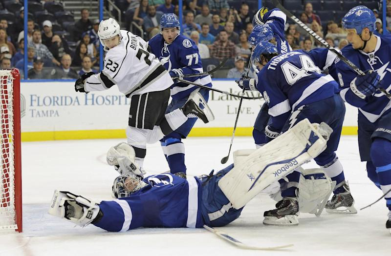 Tampa Bay Lightning goalie Ben Bishop (30) makes a sprawling save on a shot by Los Angeles Kings right wing Dustin Brown (23) as Lightning defenders Victor Hedman (77), of Sweden, Nate Thompson (44) and Sami Salo converge during the first period of an NHL hockey game Tuesday, Oct. 15, 2013, in Tampa, Fla. (AP Photo/Chris O'Meara)