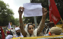 A woman farmer holds a banner during a protest in New Delhi, India, Thursday, July 22, 2021. More than 200 farmers on Thursday began a protest near India's Parliament to mark eight months of their agitation against new agricultural laws that they say will devastate their income. (AP Photo/Manish Swarup)