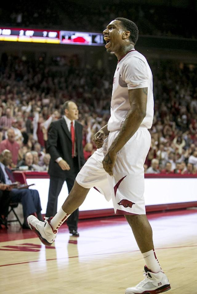 Arkansas guard Coty Clarke (4) celebrates after completing a dunk over a Georgia defender during the second half of an NCAA college basketball game on Saturday, March 1, 2014, in Fayetteville, Ark.. Clarke led the Razorbacks in scoring with 23 points as Arkansas defeated 87-75. (AP Photo/Gareth Patterson)
