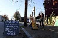 Mary Jane D'arville plays the harp while Marlysse Simmons and son Desi Alvarez, 2, listen outside of Frank Pichel's (not pictured) tree lot, Sunday, Dec. 6, 2020, in Richmond. (AP Photo/Will Newton)