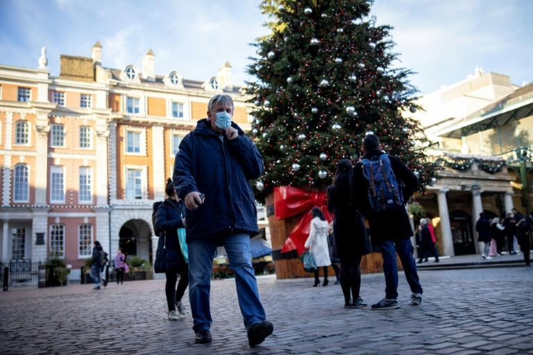 Pedestrians in face masks walk past a Christmas tree in London's Covent Garden