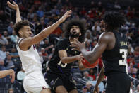 Washington's Marcus Tsohonis drives into Arizona's Chase Jeter, left, during the first half of an NCAA college basketball game in the first round of the Pac-12 men's tournament Wednesday, March 11, 2020, in Las Vegas. (AP Photo/John Locher)