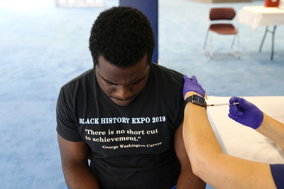 Student Willie Webb, 20, receives a shot of the Pfizer COVID-19 vaccination at St. Thomas University, Friday, Aug. 20, 2021, in Miami. The university offered a pop-up vaccination site for students on move-in day in preparation for the first day of school August 23. (AP Photo/Lynne Sladky)