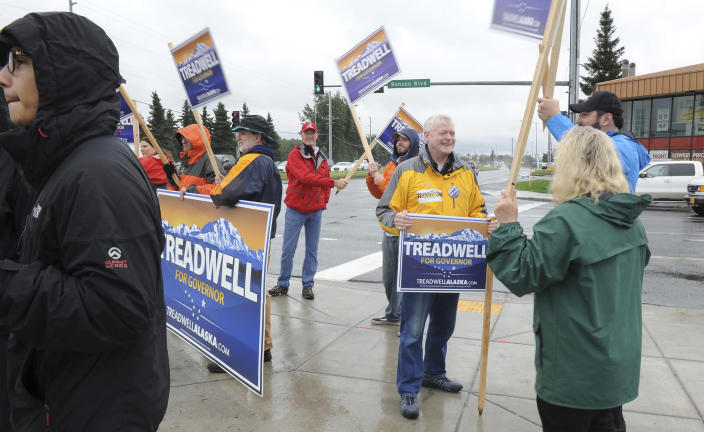 Republican gubernatorial candidate Mead Treadwell, in yellow, speaks with supporters while sign waving Tuesday August 21, 2018, in Anchorage, Alaska. Treadwell, a former Alaska lieutenant governor, is one of seven Republicans vying in the Alaska Primary. The winner advances to the general election and is expected to face incumbent Gov. Bill Walker, an independent, and former U.S. Sen. Mark Begich, a Democrat. (AP Photo/Michael Dinneen)