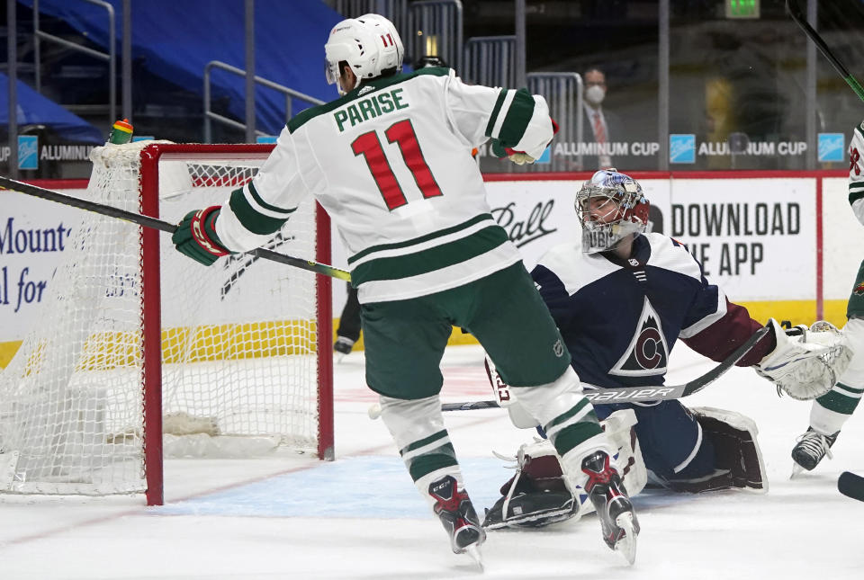 Minnesota Wild left wing Zach Parise, left, scores a goal against Colorado Avalanche goaltender Philipp Grubauer in the second period of an NHL hockey game Wednesday, Feb. 24, 2021, in Denver. (AP Photo/David Zalubowski)