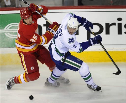 Vancouver Canucks' Christopher Tanev, right, battles for the puck with Calgary Flames' Steve Begin during first period NHL action in Calgary on Sunday, March 3, 2013. (AP Photo/The Canadian Press, Larry MacDougal)