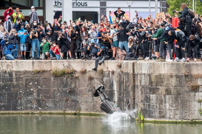 The statue of 17th century slave trader Edward Colston falls into the water after protesters pulled it down and pushed into the docks, during a protest against racial inequality in the aftermath of the death in Minneapolis police custody of George Floyd, in Bristol, Britain, June 7, 2020.(Keir Gravil via Reurters)