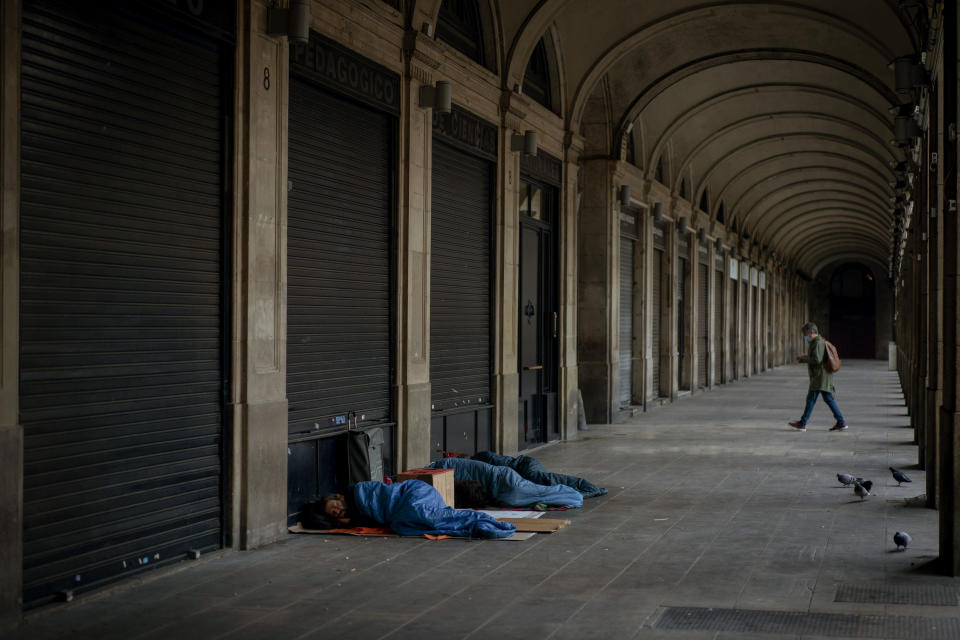 Homeless people sleep on a square where restaurants are closed due to sharpest resurgences of the new coronavirus in Barcelona, Spain, Monday, Oct. 19, 2020. Several Spanish regions adopt new restrictions to deal with the health emergency. Spain is nearing one million infections since the onset of the pandemic, the most in Europe. (AP Photo/Emilio Morenatti)