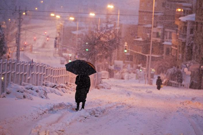 An ultra-Orthodox Jewish man walks on a snow-covered street early morning near Jerusalem's Mea Shearim neighbourhood February 20, 2015. Snow covered Jerusalem and mountainous areas of Israel early Friday morning and the education ministry closed schools for the day. (REUTERS/Ronen Zvulun)
