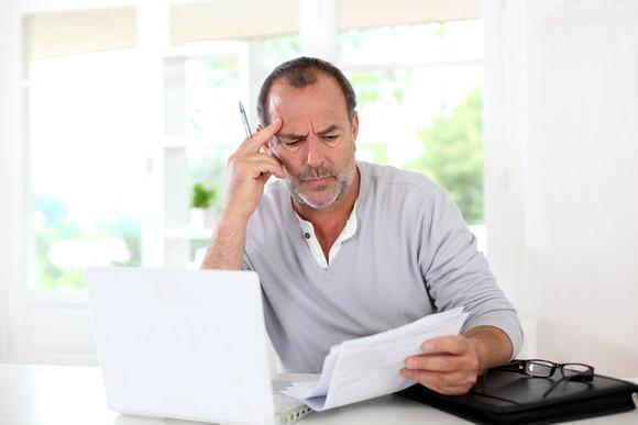 Confused and frustrated man looking at documents