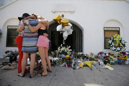 Mourners hug after praying outside the Emanuel African Methodist Episcopal Church in Charleston