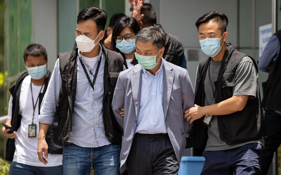 Apple Daily COO Royston Chow Tat Kuen (C) is escorted by police officers as he leaves the office - Shutterstock