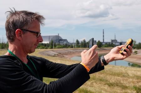 A visitor takes a picture of a dosimeter near the New Safe Confinement (NSC) structure over the old sarcophagus covering the damaged fourth reactor at the Chernobyl Nuclear Power Plant, in Chernobyl