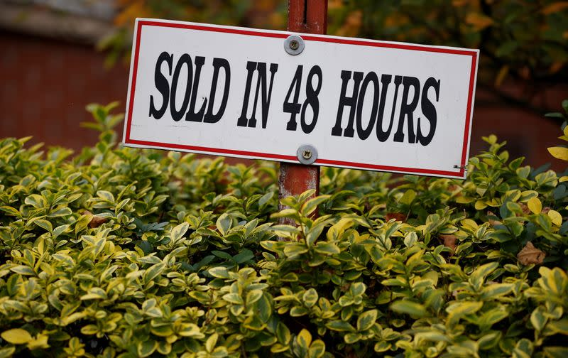A sign is pinned beneath an estate agent's board outside a housing development in Manchester