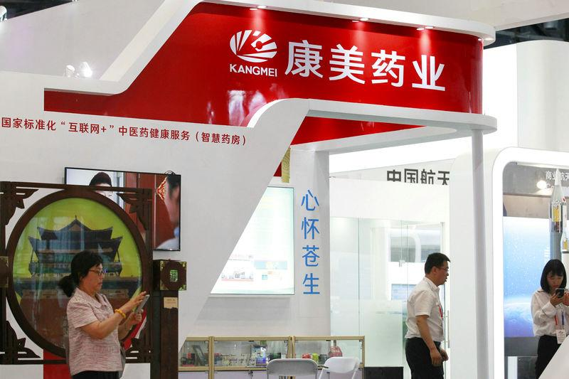 People are seen at the booth of Kangmei Pharmaceutical Co at a trade and service fair in Beijing