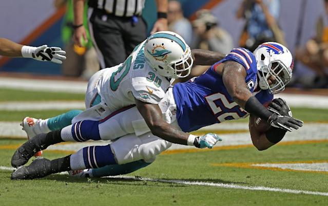 Buffalo Bills running back Fred Jackson (22) stretches for a touchdown as Miami Dolphins strong safety Chris Clemons (30) defends during the first half of an NFL football game, Sunday, Oct. 20, 2013, in Miami Gardens, Fla. (AP Photo/Wilfredo Lee)