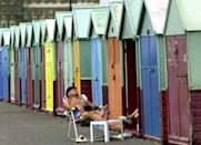 A bather optimistically hopes for sunshine in front of empty Brighton beach huts