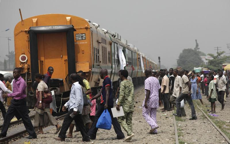 People cross the tracks as they wait for the train to move off as part of a newly inaugurated train service to Kano, Nigeria, in Lagos, Nigeria  Friday, Dec. 21, 2012.  Nigeria has rebuilt the railroad tracks connecting its commercial centre of Lagos in the south to Kano, its largest city in the north, a distance of some 720 miles (1160 Km), with Minister of Transport Idris Umar declaring a major economic boost because of the rail link.  Rail tracks connecting the cities were first built in 1912, but the connection became derelict because of corruption and neglect, until this rejuvenation of the railway system.(AP Photo/Sunday Alamba)