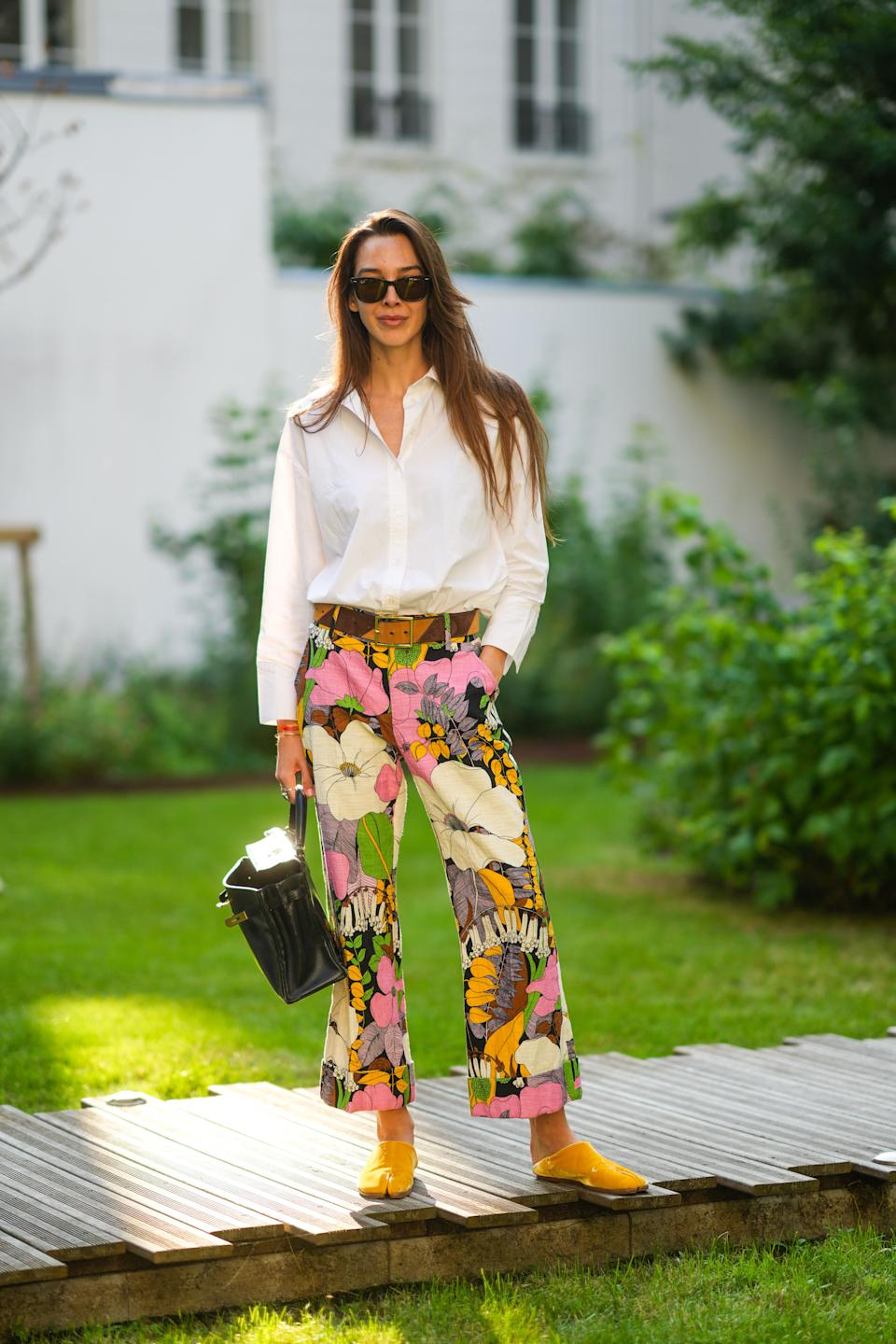 PARIS, FRANCE - JULY 01: Estelle Chemouny wears sunglasses, a white shirt, a brown striped belt, colored floral print flared pants, a black leather Hermes Birkin bag, yellow sandals / shoes, during the Twilly By Hermes : Launch Party In Paris, on July 01, 2021 in Paris, France. (Photo by Edward Berthelot/Getty Images)