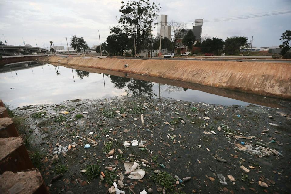 <p>A polluted canal runs past the Vila Autodromo 'favela' community next to the Olympic Park (BACKGROUND) in the Barra da Tijuca neighborhood on July 16, 2016 in Rio de Janeiro, Brazil. Nearly all of the residents of the Vila Autodromo 'favela' community in the area had their properties controversially demolished, after receiving compensation, for their homes which were located directly adjacent to the Olympic Park under construction for the Rio 2016 Olympic Games. Around 20 remaining families who continued in resistance will remain with the Rio government constructing them new homes on the property. (Mario Tama/Getty Images)</p>