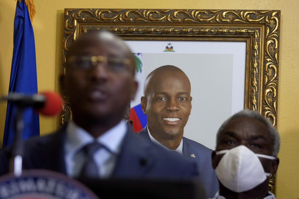 A picture of late Haitian President Jovenel Moise hangs on the wall of his former residence, behind interim Prime Minister Claude Joseph giving a press conference in Port-au-Prince, Tuesday, July 13, 2021. Moise was assassinated in his home on July 7. (AP Photo/Joseph Odelyn)