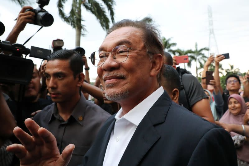 Malaysian politician Anwar Ibrahim waves to his supporters after a news conference in Petaling Jaya