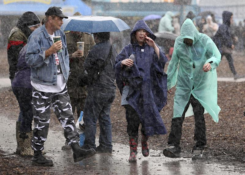 Festival goers brave the falling rain at the Hard Rock Calling music festival in Hyde Park, London, Friday, July 13, 2012.  The weekend music event was planned to be held on the grass of Hyde Park, but the land turned into a muddy quagmire and had to be covered with wood chips to enable the festival to go ahead,  as part of the build-up to the upcoming 2012 London Olympic Games. (AP Photo / Lewis Whyld, PA) UNITED KINGDOM OUT - NO SALES - NO ARCHIVE