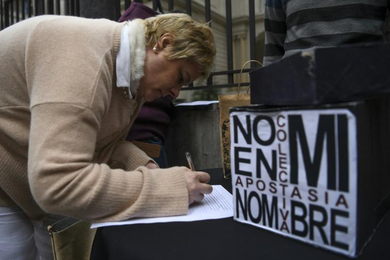 A woman signs a form  to renounce their religious affiliation to the Catholic Church, one of thousands of Catholics angered at the church's role in opposing a bill that would have decriminalized abortion