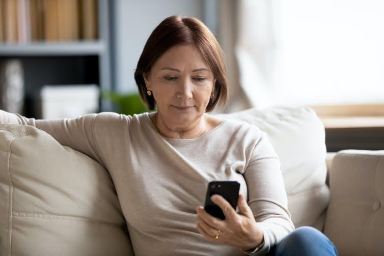 A woman sits on the couch looking at her smartphone.