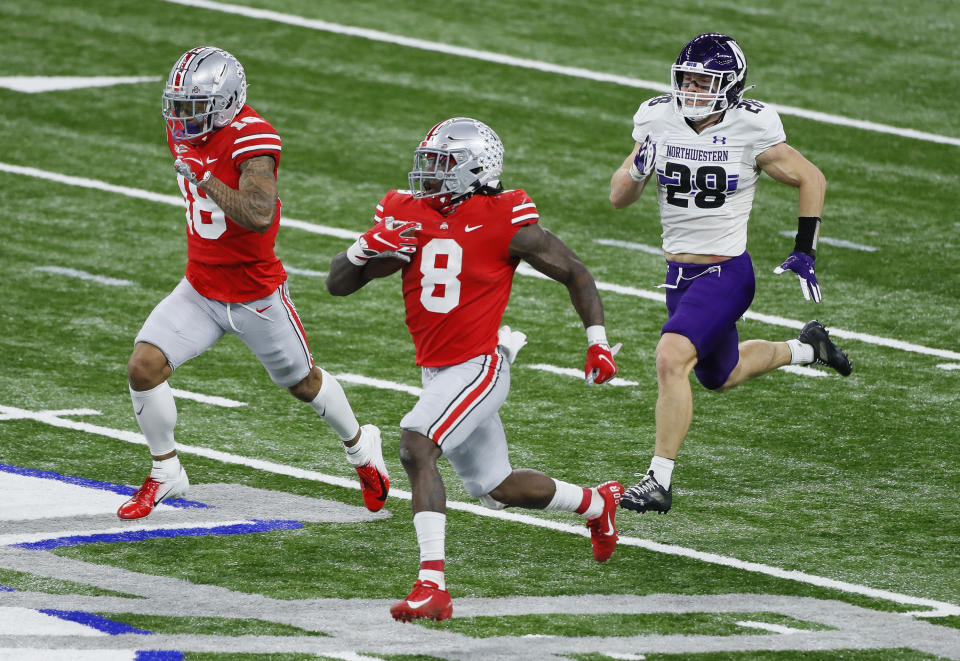 Dec 19, 2020; Indianapolis, IN, USA; Ohio State Buckeyes running back Trey Sermon (8) rushes for 65 yards ahead of wide receiver Kamryn Babb (18) and Northwestern Wildcats linebacker Chris Bergin (28) during the third quarter of the Big Ten Championship football game at Lucas Oil Stadium in Indianapolis on Saturday, Dec. 19, 2020. Ohio State won 22-10. Mandatory Credit: Joshua A. Bickel-USA TODAY NETWORK
