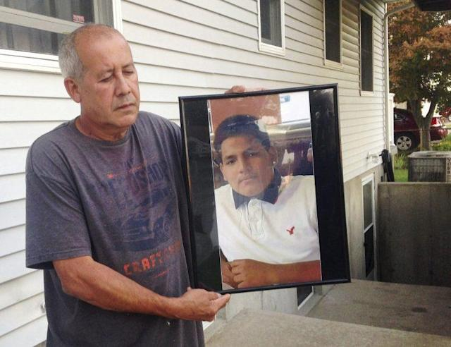 Abraham Chaparro holds a photograph of his murdered stepson, Miguel Garcia-Moran, outside his home in Brentwood, N.Y. (Photo: Claudia Torrens/AP)