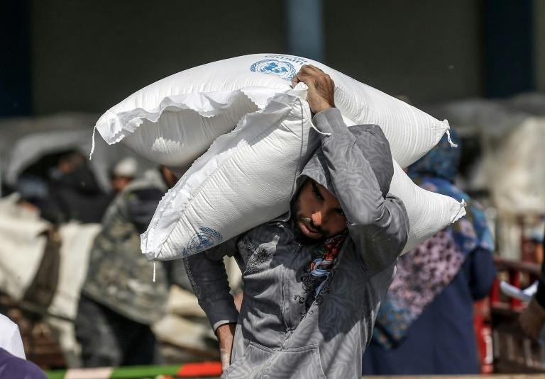 A Palestinian man carries sacks of flour received from a UNRWA distribution centre in the southern Gaza Strip refugee camp of Rafah in November 2019