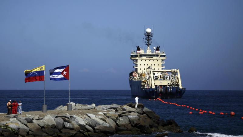 FILE - In this Jan. 22, 2011 file photo, people stand on a breakwater, with a Venezuelan flag, left, and a Cuban flag, as a specialized ship rolls out a fiber-optic cable, suspended from buoys, off La Guaira, Venezuelan coast. Cuba's state telecom monopoly confirmed Thursday, Jan. 24, 2013 that the island's first hard-wired Internet connection to the outside world has been activated, but said it won't lead to an immediate increase in access. The $70 million ALBA-1 arrived on the island from Venezuela in February 2011 to great hoopla, but officials soon stopped mentioning the cable amid rumors of mismanagement and corruption involving the project.  (AP Photo/Ariana Cubillos, File)