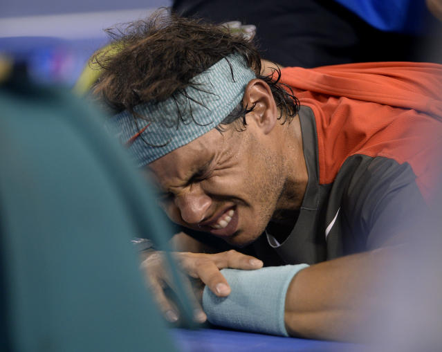 FILE - In this Jan. 26, 2014, file photo, Rafael Nadal of Spain grimaces as he receives a medical treatment to his back in the men's singles final against Stanislas Wawrinka of Switzerland at the Australian Open tennis championship in Melbourne, Australia. Nadal had stem cell treatment in 2014 to help his ailing back but hasn't endorsed the procedure.(AP Photo/Andrew Brownbill, File)